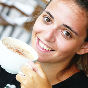 student smiling with coffee